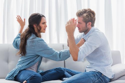 Upset woman about to slap her partner the living room