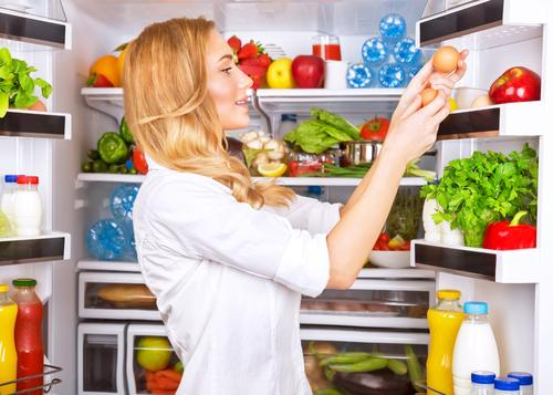 Woman getting eggs from refrigerator