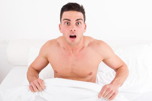 Surprised and shocked half naked young man in bed looking down at his penis