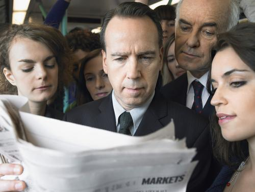 Group of commuters reading newspaper in the train