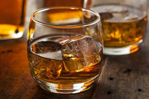 Alcoholic amber whiskey bourbon in a glass with ice