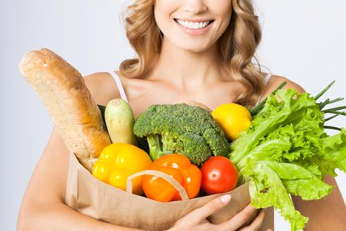 Woman smiling holding grocery bag with vegetables