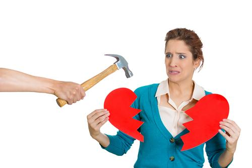 Woman holding broken heart from hammer