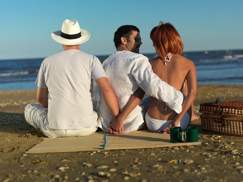 Woman talking with the boyfriend, while holding hands with another man, at a picnic by the sea shore