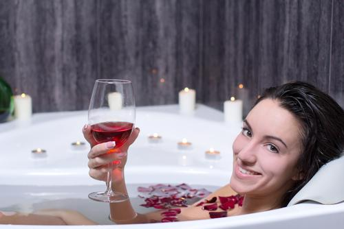 Woman in bath with rose petals drinking wine