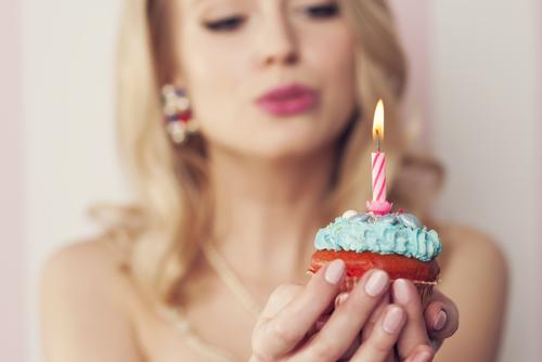 Woman blowing birthday candle on cupcake