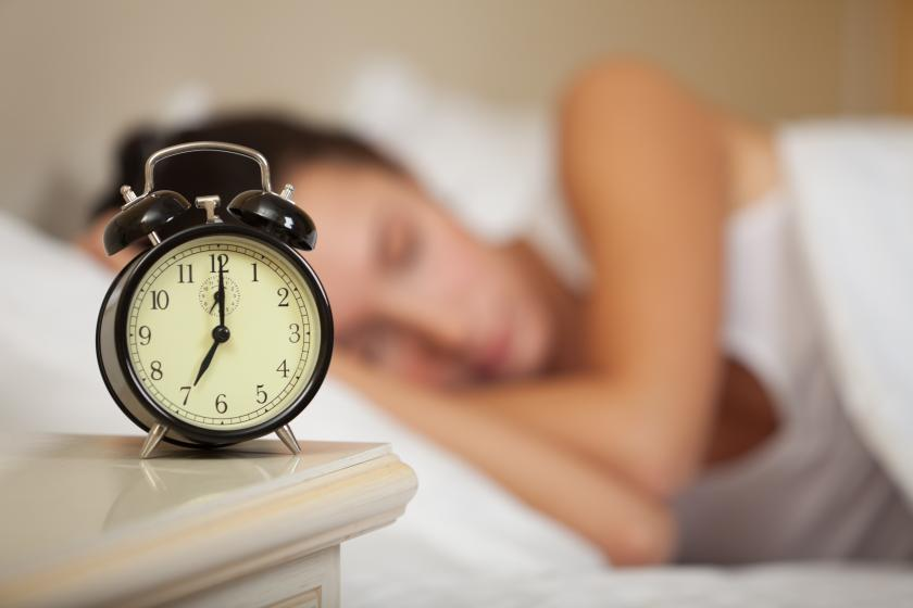 Sleeping woman and alarm clock in bedroom at home