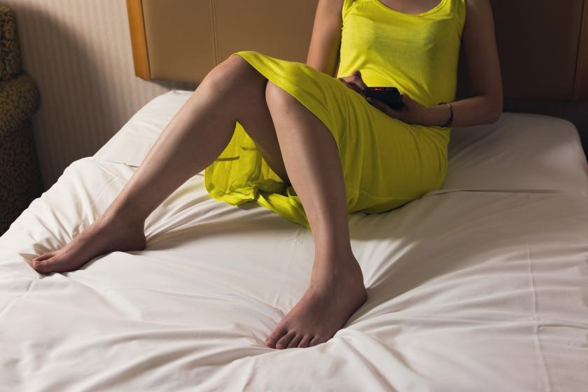 Woman sitting on bed using cellphone