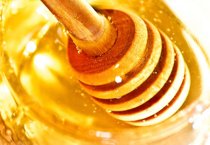 Honey background with wooden dipper
