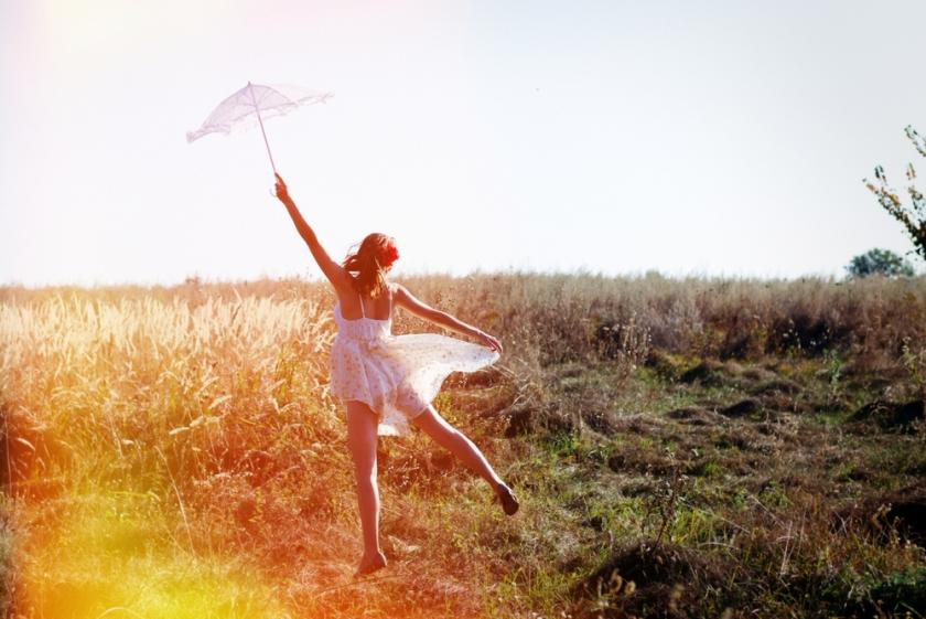 Woman alone in the field with umbrella