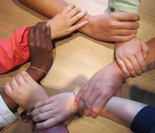 Hands of different races holding wrists