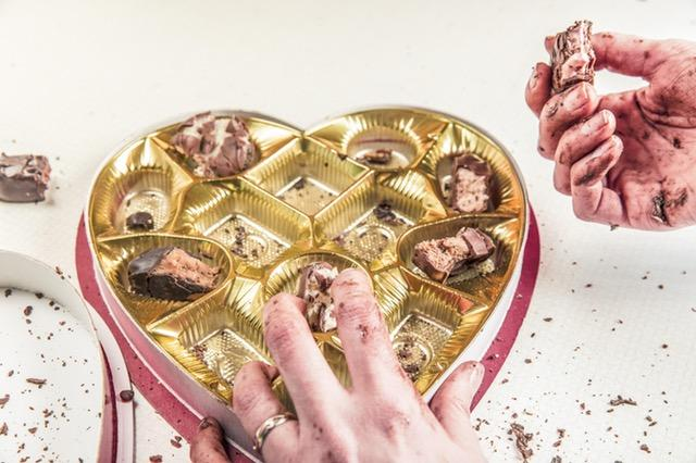 Eating chocolate from heart-shaped box