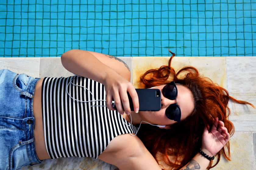 Woman on phone lying next to pool