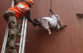 A fire fighter evacuates a patient from a hospital after it caught fire in Kolkata December 9, 2011.