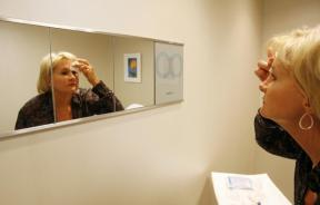 A woman looks at herself in a mirror after receiving a Botox injection at a walk-in Botox salon