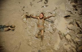 A boy plays in the mud on the bank of the Bago river in Bago March 20, 2012.
