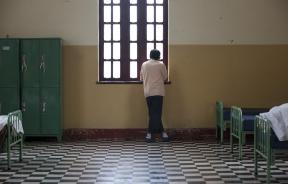A patient looks through a window inside the Larco Herrera psychiatric hospital in Lima