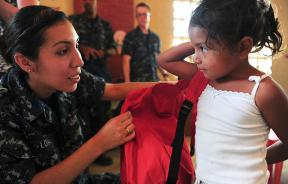 Sailor helps a student in Ecuador with a donated backpack