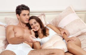 Happy couple watching TV in bedroom