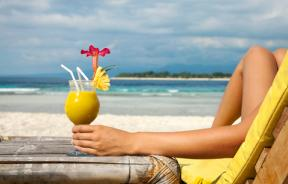 Woman having cocktail on the beach