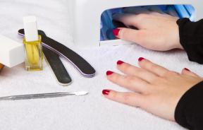 womans-hands-under-uv-lamp-nails