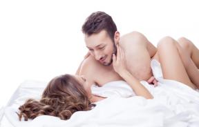Man smiling looking at woman in bed