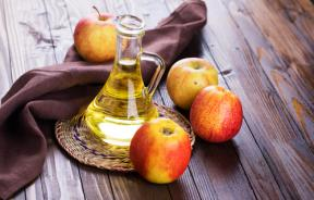 Apple vinegar and apples on wooden table