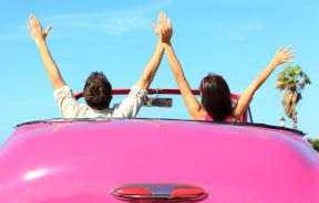 Happy free couple in car driving in pink vintage retro car