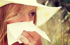 Woman with tissue covering nose