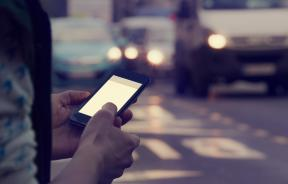 Man using cellphone outdoors with traffic in the background