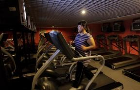 A woman runs on a treadmill.