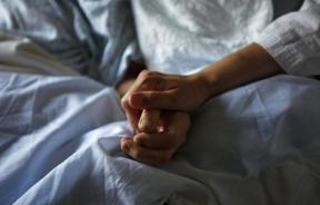 A woman holds hands with her ailing mother.