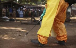 A healthcare workers disinfects the surrounding area.