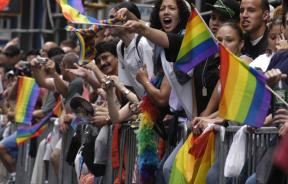 Parade goers wave flags during the LGBT Pride March in NYC.