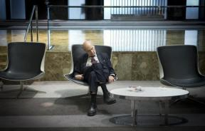 A businessman naps while sitting in the lobby of a hotel.