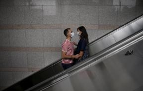 A couple wears masks as they ride on an escalator.
