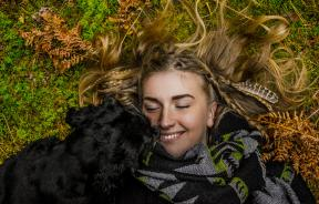 Girl lying on grass with dog