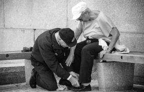 Man tying woman's shoe